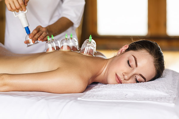 Woman laying on chest with cupping treatment on back